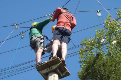 Climbing a wobbly pole together and lean back! High level ropes course Forest of Dean, Wye Valley, South Wales